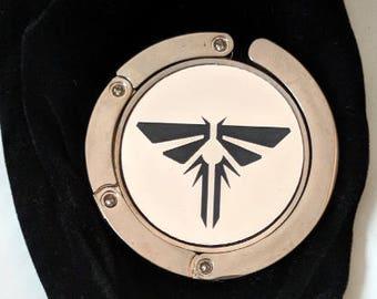 The Last of Us Fireflies symbol purse hanger, laser engraved. Comes with an elegant black velvet pouch. TLOU TLOU2