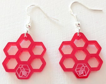 Honeycomb earrings, laser cut from semi-transparent red acrylic, with a little bee.