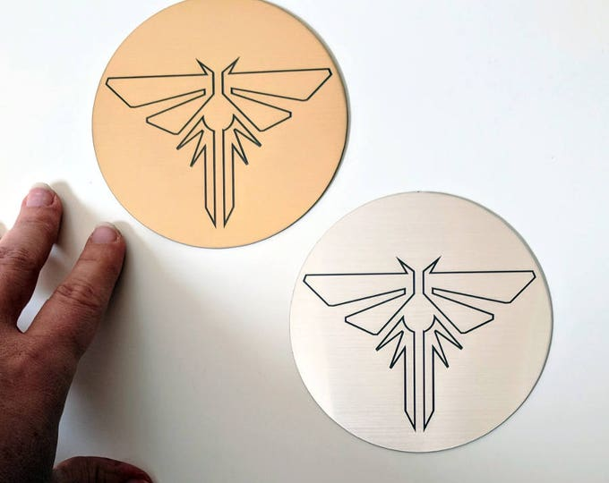 The Last of Us sticker, metallic silver and gold. Fireflies symbol from TLOU and TLOU2, laser engraved. Great for laptops!