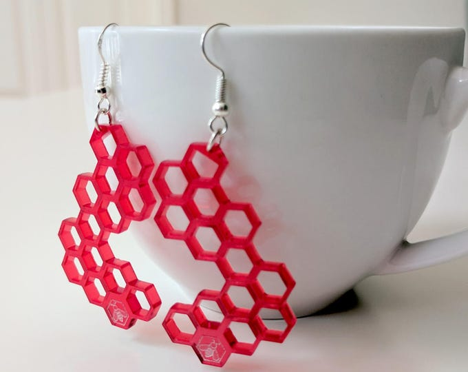 Honeycomb earrings, laser cut from semi-transparent red acrylic, with a little bee, laser engraved