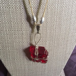 Strawberry Red Andara with a braided red leather necklace.