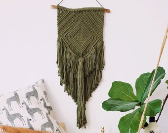 Ami - medium macrame wallhanging / tapestry made from green colored cotton with a chunky tassel and woven details