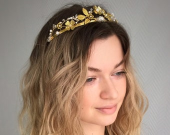 Wedding tiara with metal leaves and flowers of gold color, white pearl and translucent beads