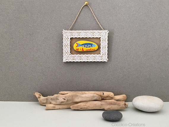 Pebble painted sardine on cardboard and lace frame
