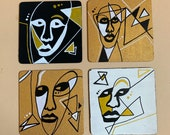 Funky faces in gold, white and black. Abstract face coasters on wooden coaster set of 4