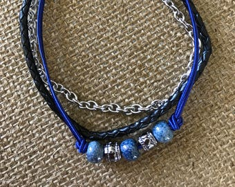 Triple strand blue bracelet with heart shaped toggle clasp.  Blue silk, braided leather and silver chain.   9""