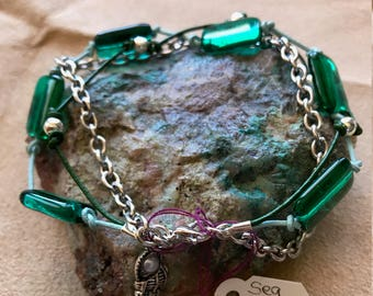 Dark Green sea glass triple strand bracelet .   Also has a seashell charm.  8""