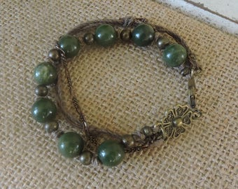 Green and bronze triple strand.  Lovely bronze medallion by the lobster clasp.  8""