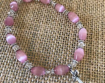 """Rose pink with swarovski crystals and silver beaded bracelet with dangling cross charm.  7 1/2"""" stretch band"""