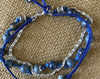 Dark blue triple strand bracelet.  Knotted hemp, silk cord and silver chain.  Even with 3 strands it is very light on your wrist.  8 1/2""