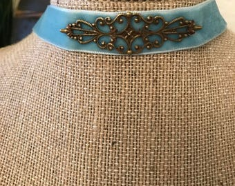"""5/8"""" turquoise suede choker with an antique bronze metal filigree pendant attached"""