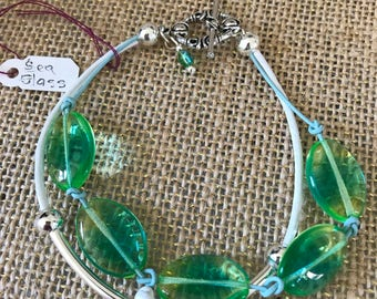 Green sea glass and white leather double strand.  Closes with a toggle clasp.  8 1/2""