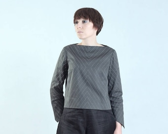 grey blouse with boat neckline, graphic symmetric pattern, interesting detail at the sleeve hem