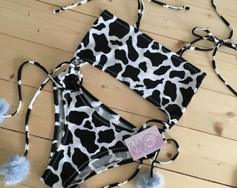 Cow print bodysuit with faux fur pom poms
