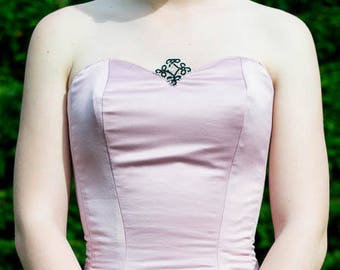 Pointed corset with a jewel in the neckline.
