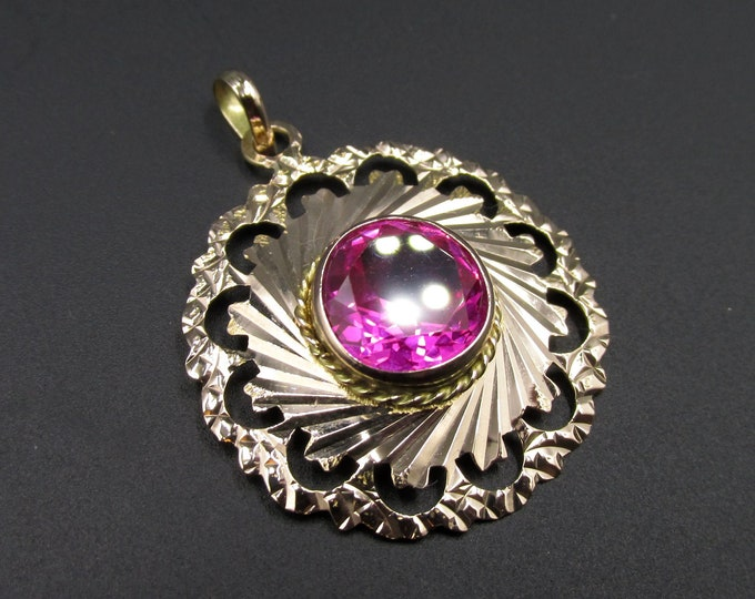 Featured listing image: A 14-karat gold women's pendant from the middle east in a round shape and set with a pink stone (tourmaline?).