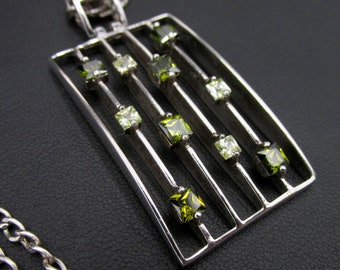 Large silver women's necklace with its rectangular pendant in modern minimalist style green square stones