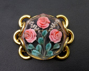 Vintage brooch with a floral theme made of gold metal and transparent resin with engraved flowers, carved.
