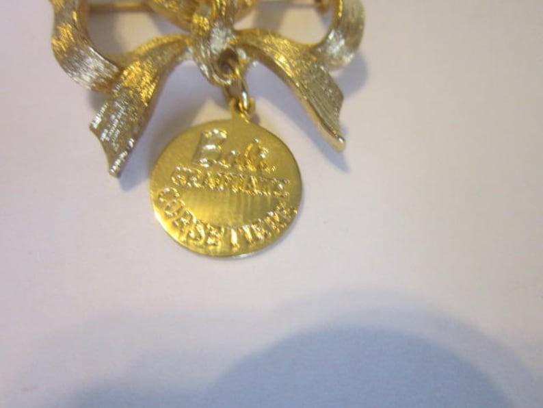 Vintage Gold Tone Bow Brooch Bali Graduate Corsetiere Badge Pinback