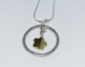 Handmade sterling silver ,hammered ring with a brass flower centrepiece