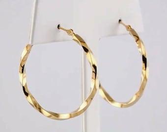 14k yellow gold twisted designer hoop earrings.