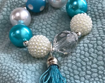 Blue & White Delight.   Chunky blue sparkly bracelet with tassel and added silver tone charm upon request .