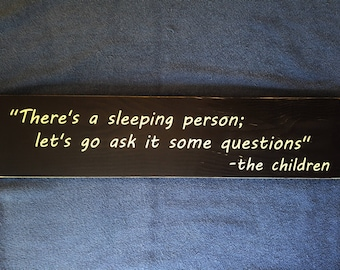 There's a sleeping person; let's go ask it some questions -the children wooden sign