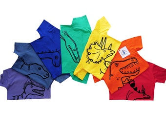 Pack of 7 Kids Dinosaur T.shirts. Colours of the rainbow! Sent in a rainbow mailing bag!