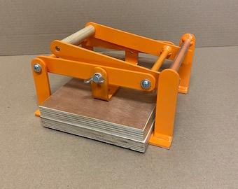 A5-size (junior legal+) hand lino press, lino cut press, heavy duty, steel, powdercoated orange ral 2003