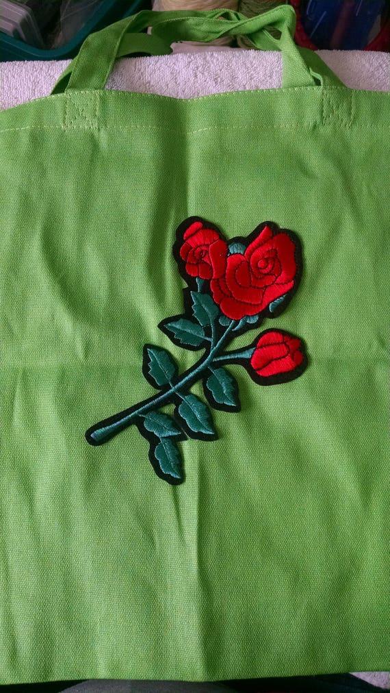 Sac cabas vert avec une rose rouge