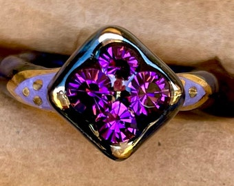 Discounted Size 8.25 Blue and grey speckled black and lavender ceramic ring with 22kt gold accents and purple glass rhinestones.