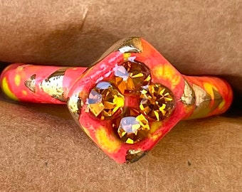Discounted Size 10.25 yellow, green and orange speckled red ceramic ring with 22kt gold accents and burnt orange glass rhinestones.