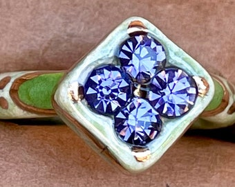 Discounted Size 6 speckled light green ceramic ring with 22kt gold accents and lavender glass rhinestones framed by dark green detailing.