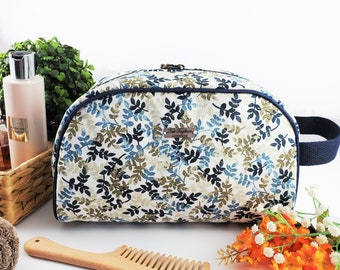 Half Moon toiletry bag made of cotton and structured for form, zippered taco pouch with handle - blue, navy, and beige flower branches
