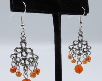 Orange chandelier earrings in glass and silvery metal