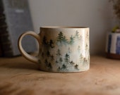 Pottery mug with foggy forest.
