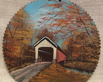 Rustic Vintage Hand Painted metal gear plate  / disc / 9 1/2  inches in diameter / hanger  / scenic fall trees and old covered bridge