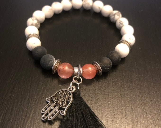 White howlite beaded bracelet with black tassel and hamsa hand.