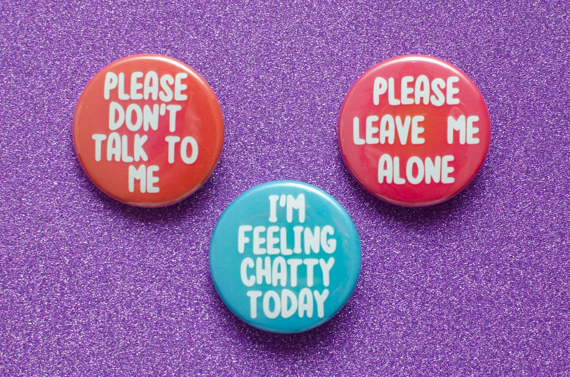 """Three pins with the words """"Please don't talk to me,"""" """"Please leave me alone"""" and """"I'm feeling chatty today"""""""