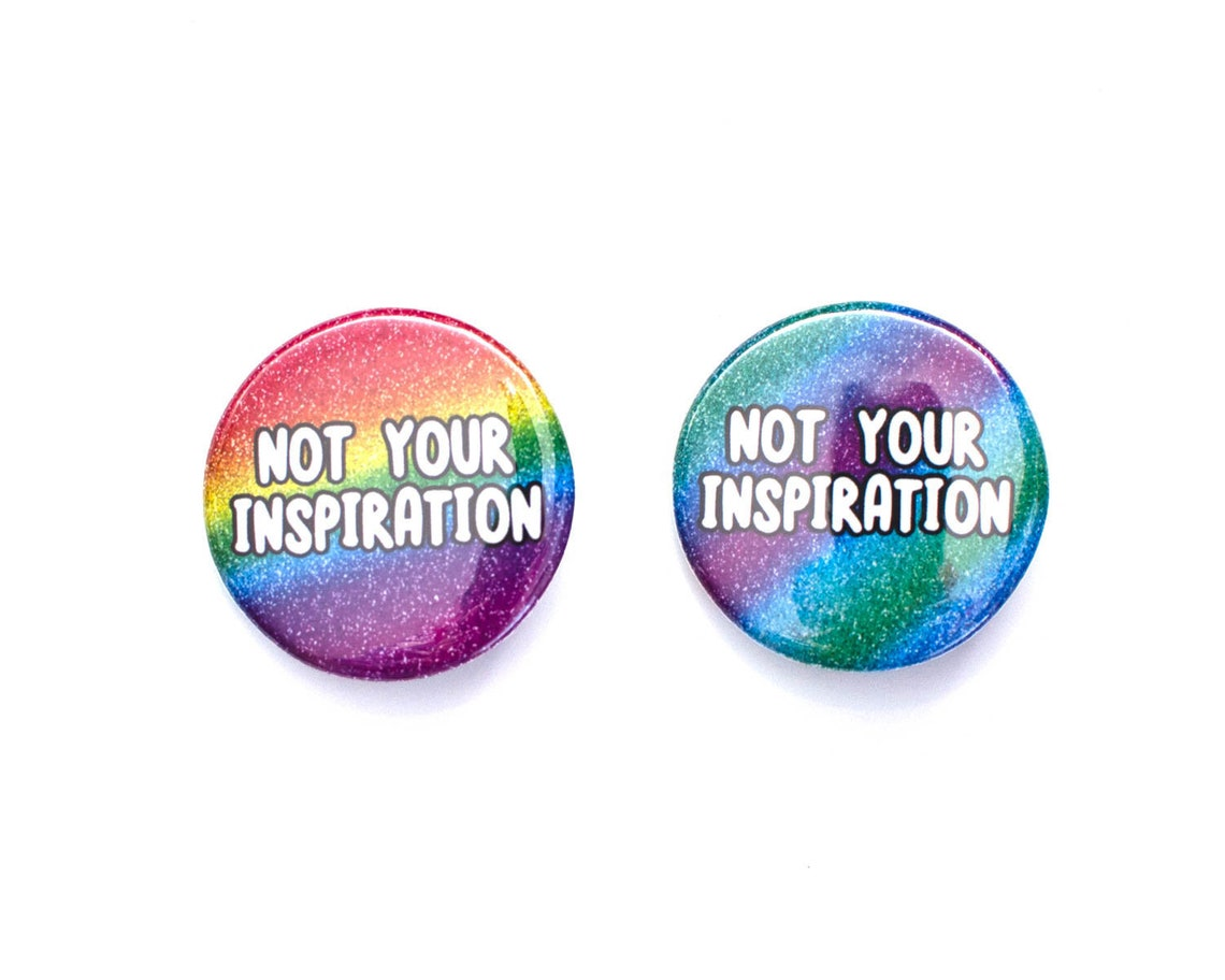 """Two rainbow glitter pins with the words """"Not your inspiration"""""""