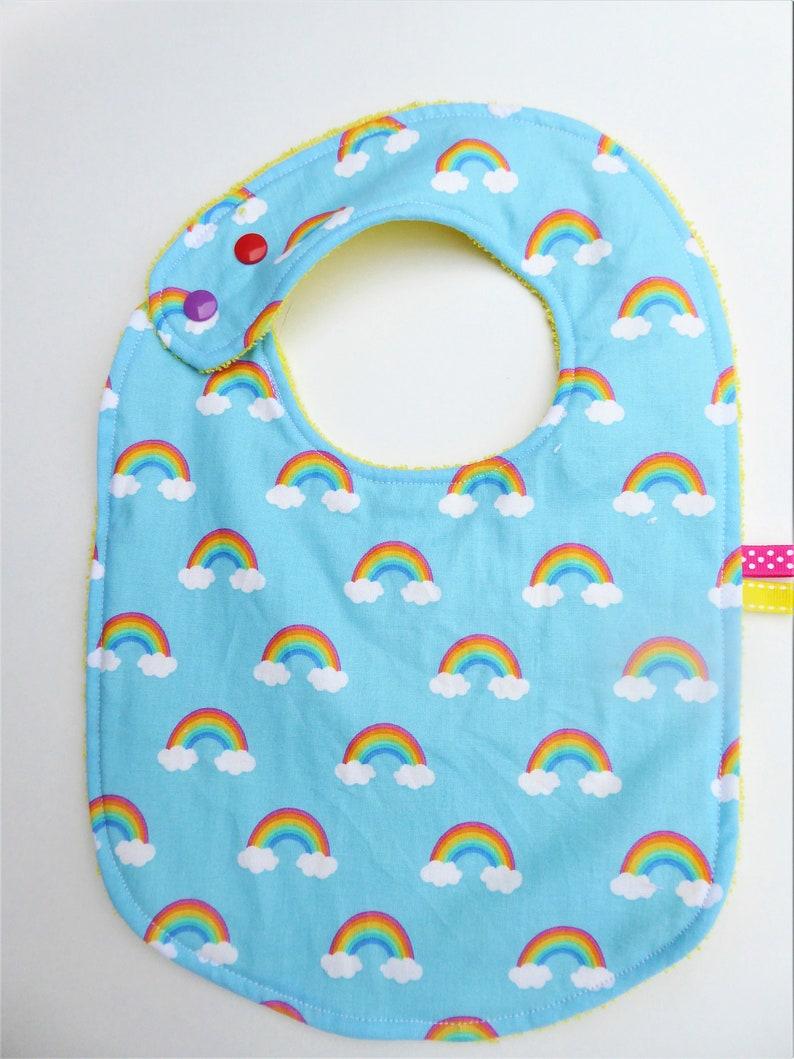 rainbow patterns and yellow sponge. Baby girlboy bib 0-12 months blue-bottomed cotton fabric