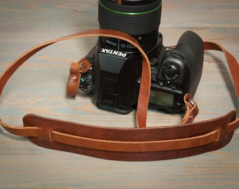 Hand made in the UK, leather copper riveted camera strap with moveable shoulder pad.