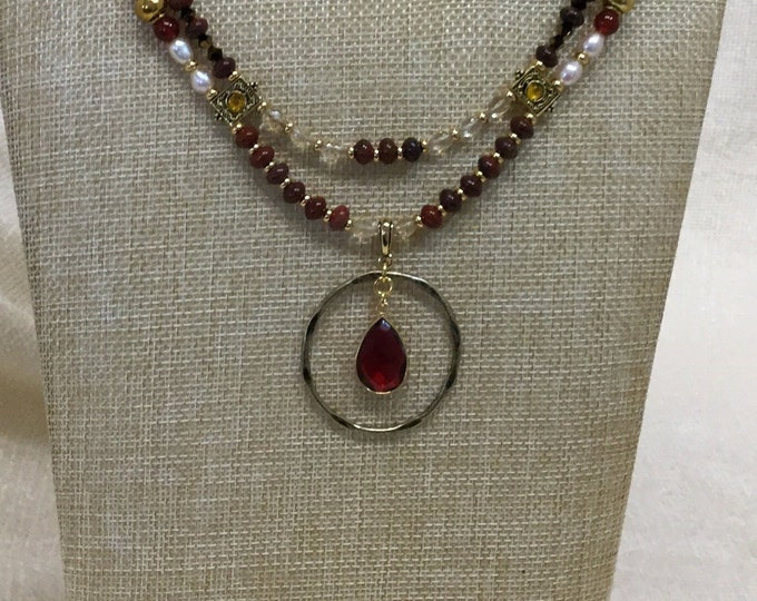 Double-strand pendant length necklace with hammered brass ring and ruby colored drop.