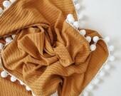 waffle knit pom pom swaddle blanket