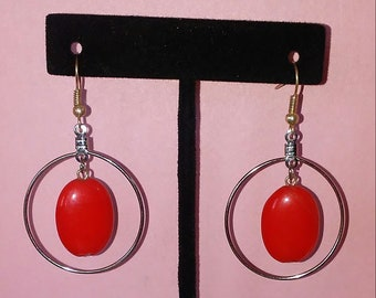 Hoop earrings with red glass bead accent.