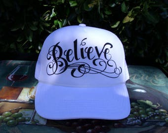 All white trucker hat with Belive emossed in a glitter font