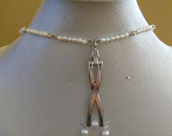 Pearl necklace with abstract X pendant