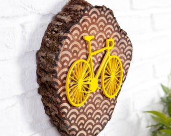 Slice of trunk with geometric waves and yellow bicycle in relief engraving