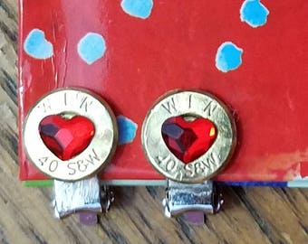 Clip on earrings. 40 cal gun casing with crystal swarovski bling heart in the center of bullet. Bullet art