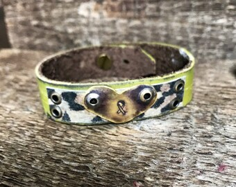 Cancer stamped heart on moss green leather cuff. Leopard accent riveted.